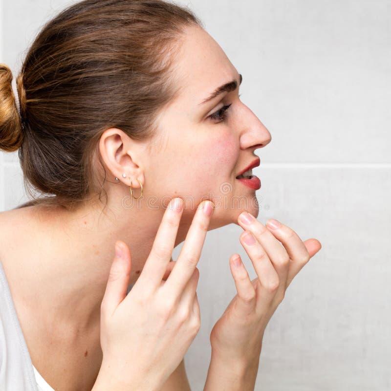 有粉刺的女性少年检查她的zits、丘疹或者伤疤的 库存照片