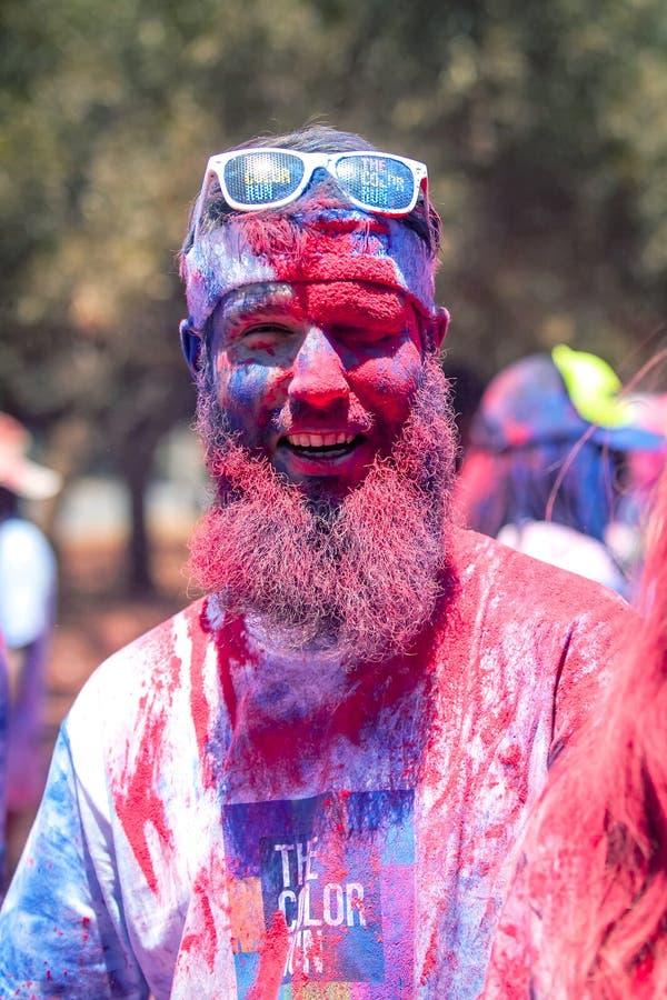 有粉末的赛跑者在他的在颜色奔跑的面孔 库存图片