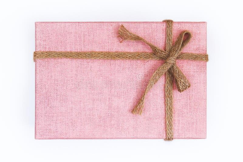 有粗麻布丝带和弓的桃红色礼物盒 免版税图库摄影