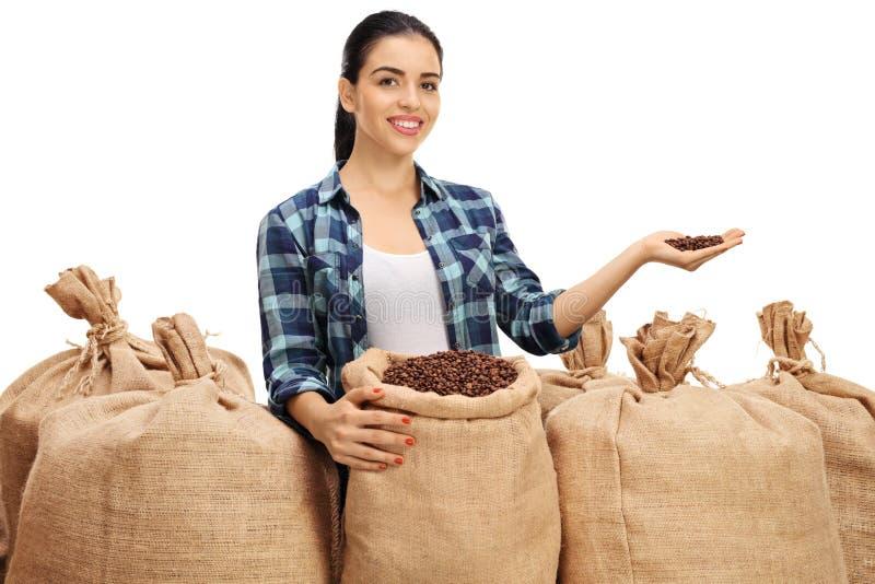 有粗麻布的女性农夫袋装给咖啡豆 库存照片