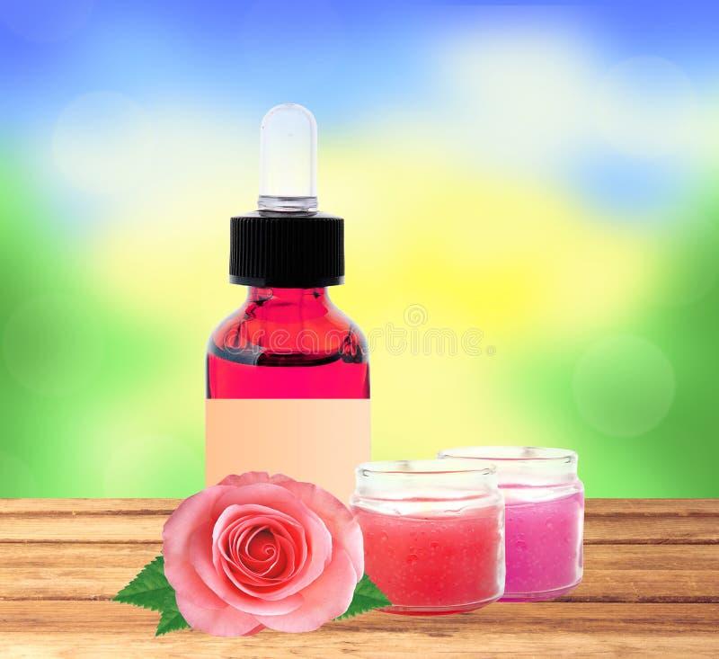 有精华油和玫瑰色花的瓶在na的木桌上 图库摄影