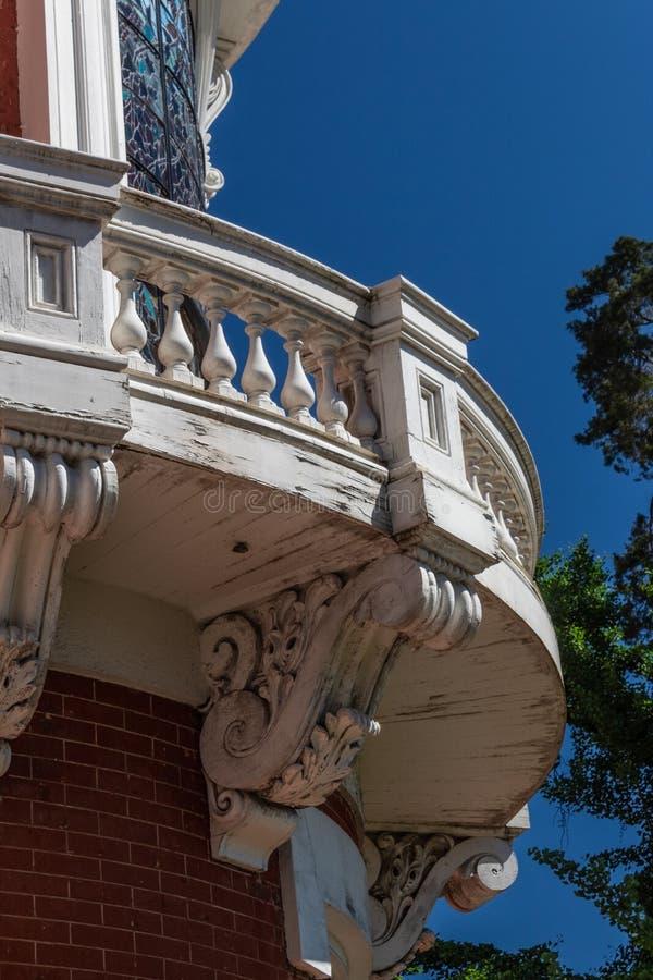 有精心制作的梁托的弯曲的外部木阳台 免版税库存照片