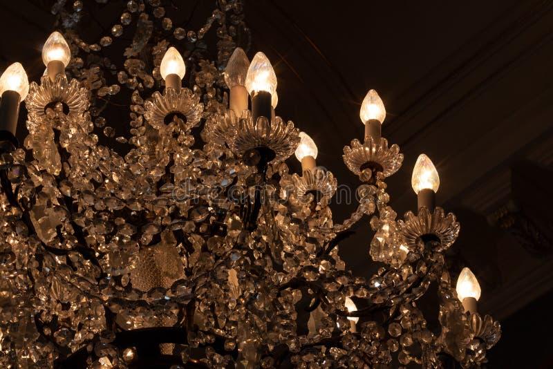 有精心制作的水晶的美丽的枝形吊灯在一个暗室 库存图片