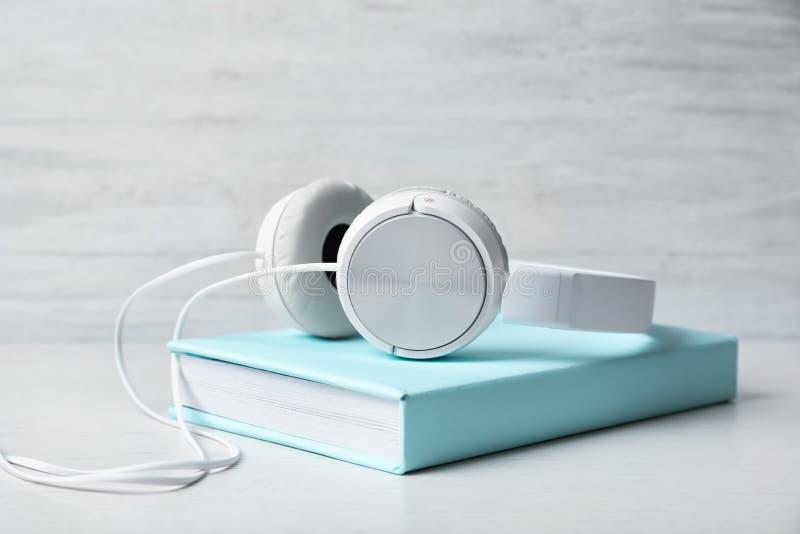 有精装书的现代耳机在木选项 库存图片
