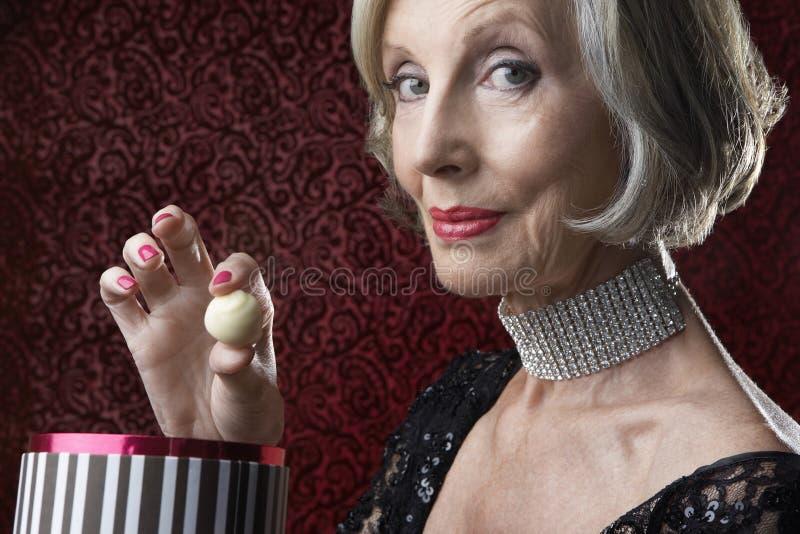 有糖果箱子的富裕的资深妇女 免版税库存图片