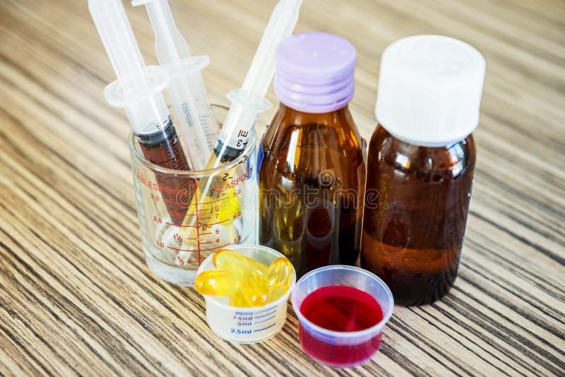 有糖浆医学和药片用途的注射器为孩子哺养 图库摄影