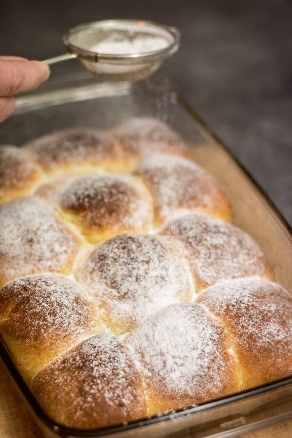 有糖筛子和束的手小圆面包 库存照片