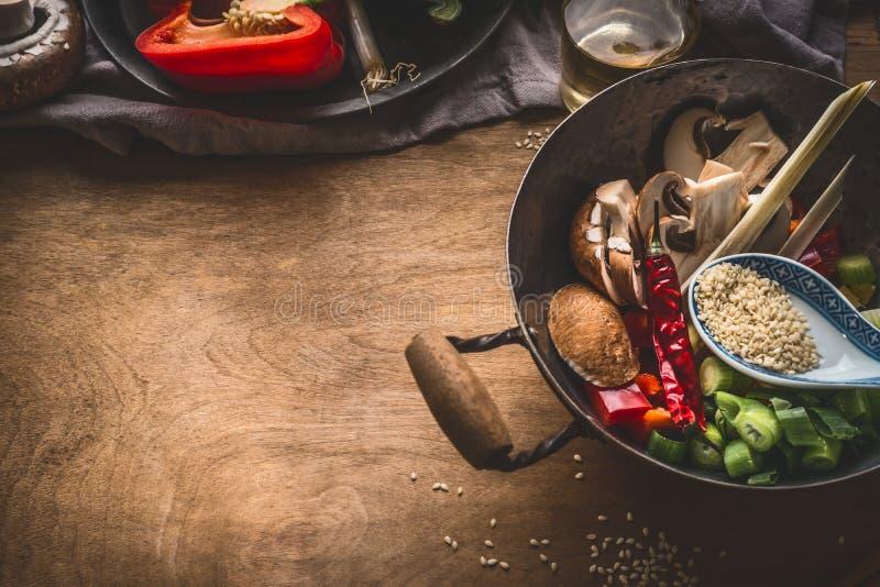 有素食亚洲烹调成份的铁锅罐与切好的菜、香料、芝麻籽和柠檬香茅的混乱油炸物的在鲁斯 免版税库存照片