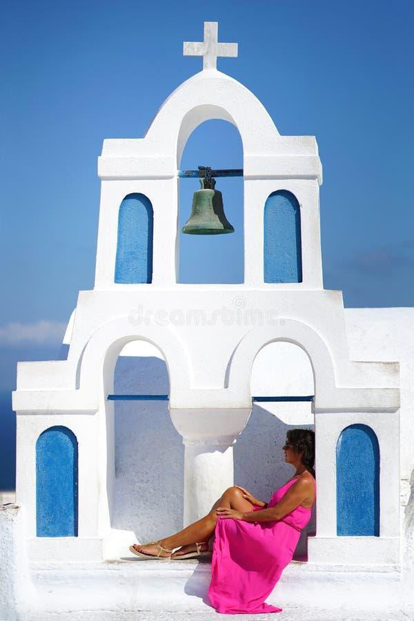 有紫红色的礼服的妇女在一个小教会的钟楼坐在Oia在圣托里尼 免版税图库摄影