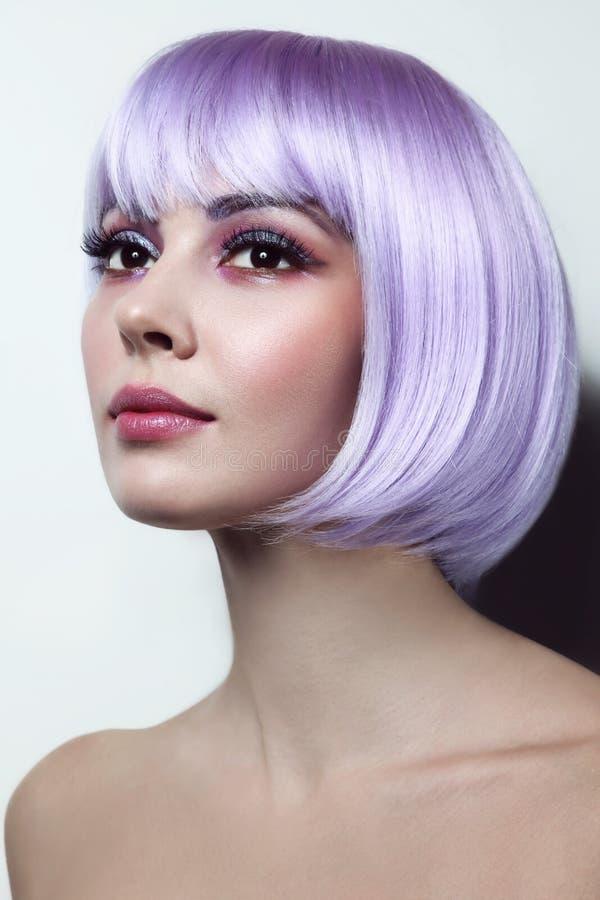 有紫罗兰色头发的年轻美丽的女孩和花梢化妆 库存图片
