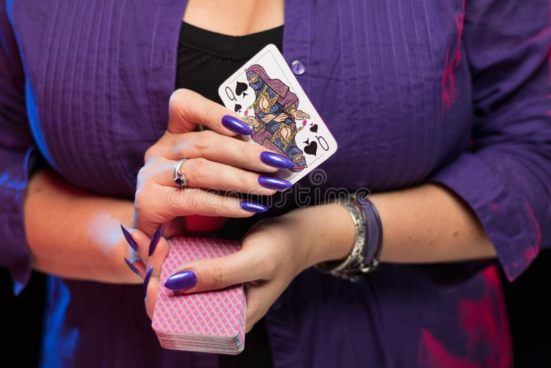 有紫色修指甲的女性手拿着戏剧卡片甲板  免版税库存照片