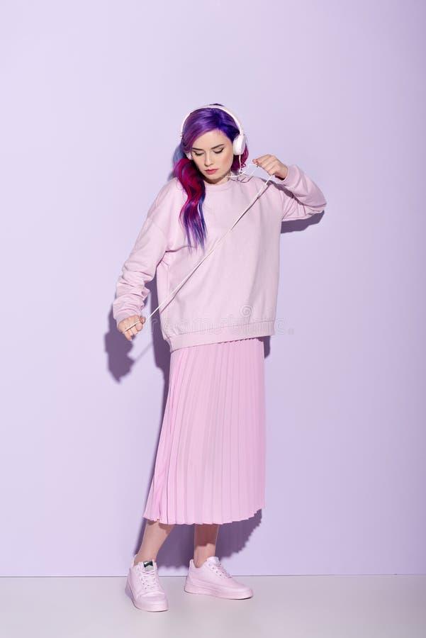 有紫色头发的跳舞的年轻女人在桃红色衣裳听的音乐 免版税图库摄影