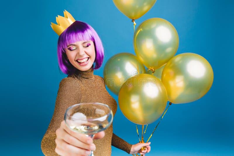 有紫色理发、冠在庆祝与金黄气球的头和香槟的愉快的年轻女人在蓝色背景 免版税库存照片