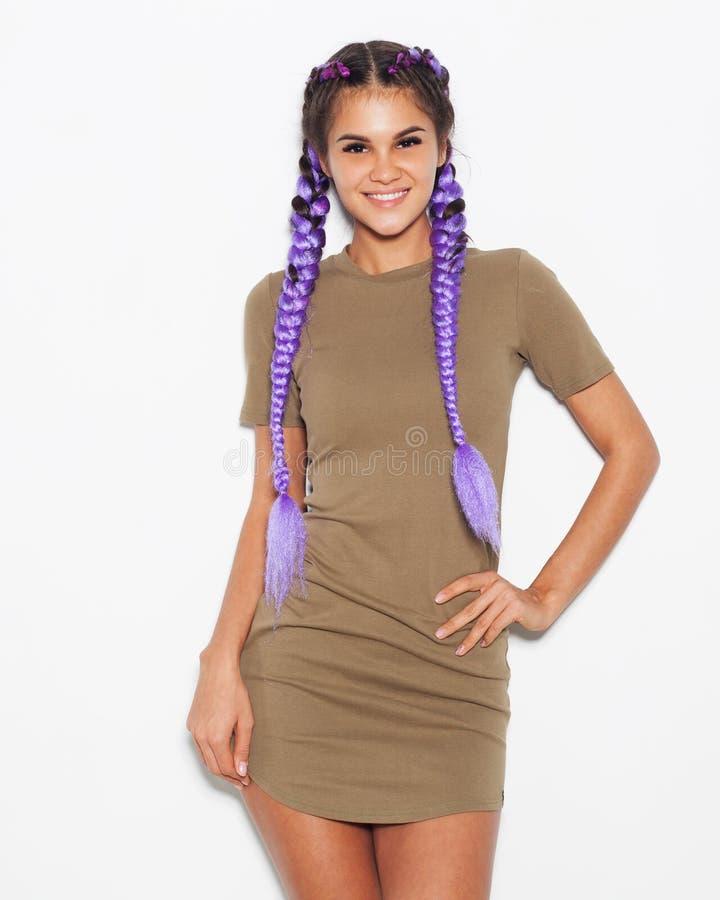有紫色辫子的俏丽的女孩在摆在反对白色背景的一件时兴的礼服 免版税库存照片