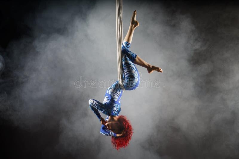 有红头发人的运动性感的空中马戏艺术家在做把戏的蓝色服装在空中丝绸 免版税库存图片