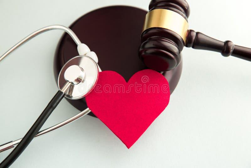 有红心、药片、听诊器和书的惊堂木在桌上 医疗法律 免版税库存照片