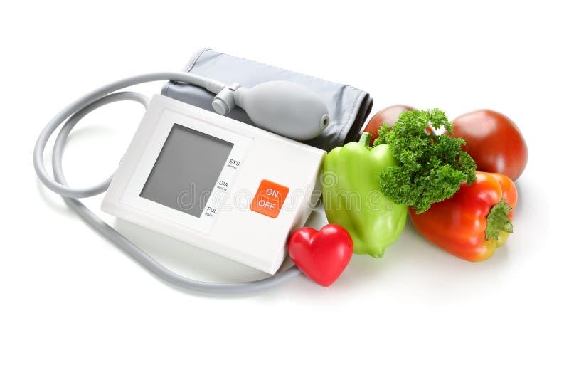 有红心的在白色背景的血压计和菜 库存图片