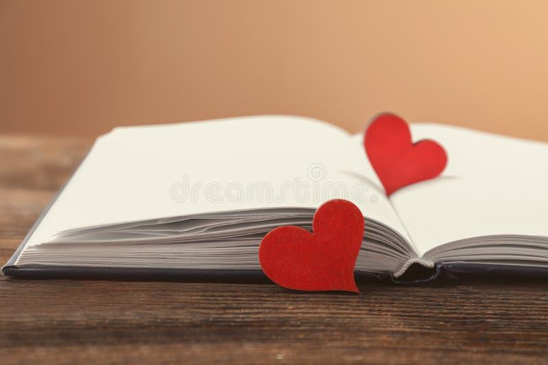 有红心的开放笔记本在木桌上 图库摄影