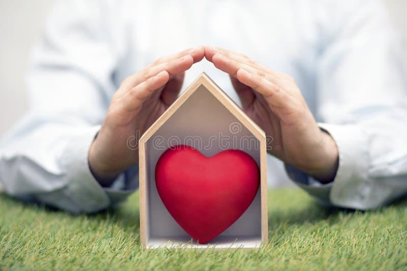 有红心的木房子在手的保护的绿草 免版税图库摄影