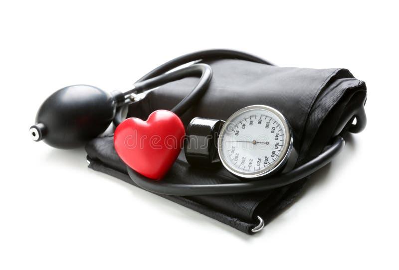 有红心的血压计在白色背景 图库摄影