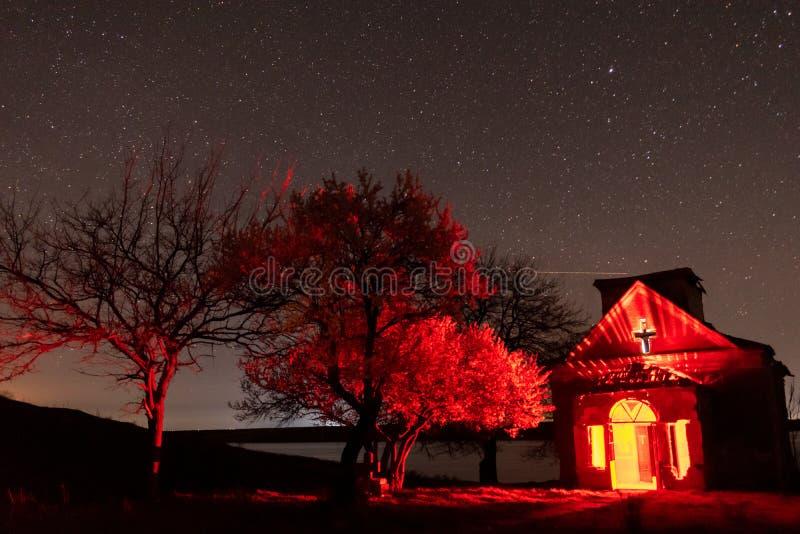 有红灯里面和开花的树附近的nightscape的被放弃的教会 图库摄影