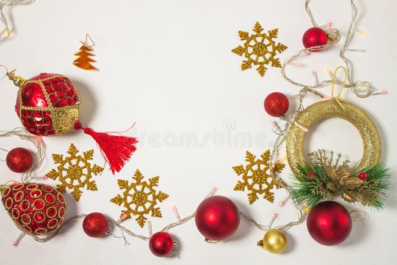 有红色丝带、金装饰、球、雪花和光的圣诞礼物箱子在白色背景 库存照片