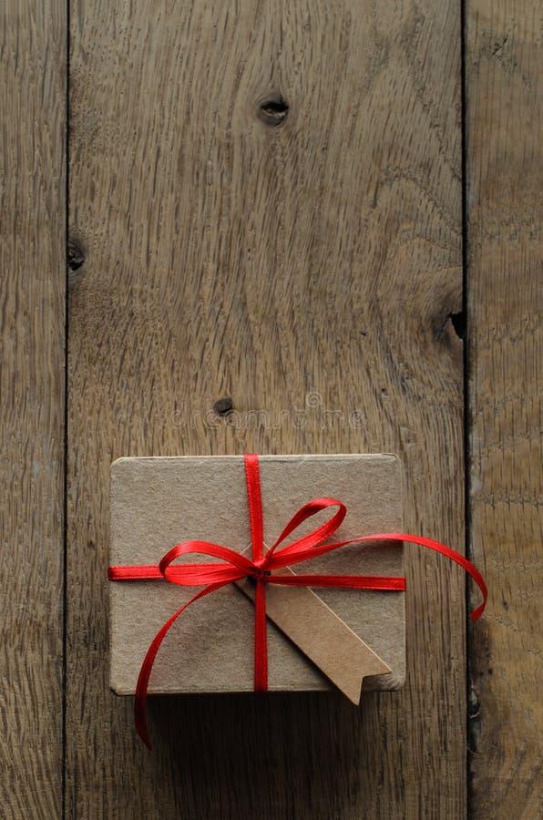 有红色丝带和葡萄酒样式空白标记的简单的布朗礼物盒 免版税库存图片