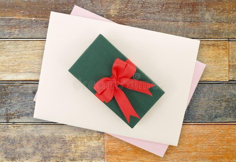 有红色丝带弓的小绿色礼物盒和与浅紫色的贺卡的白色信封在木桌地板上 免版税库存图片