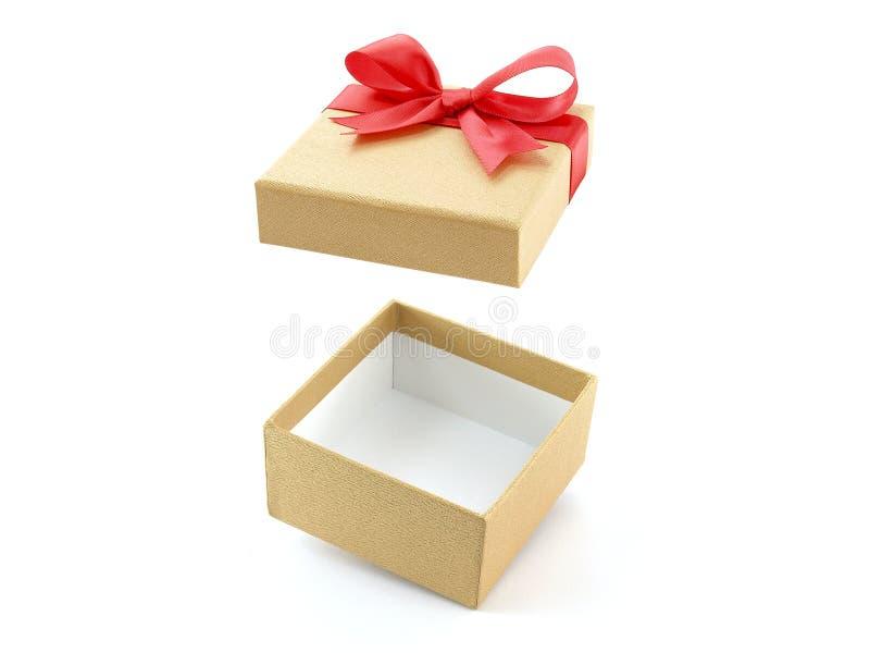 有红色丝带弓的开放和空的金黄礼物盒在白色背景 图库摄影