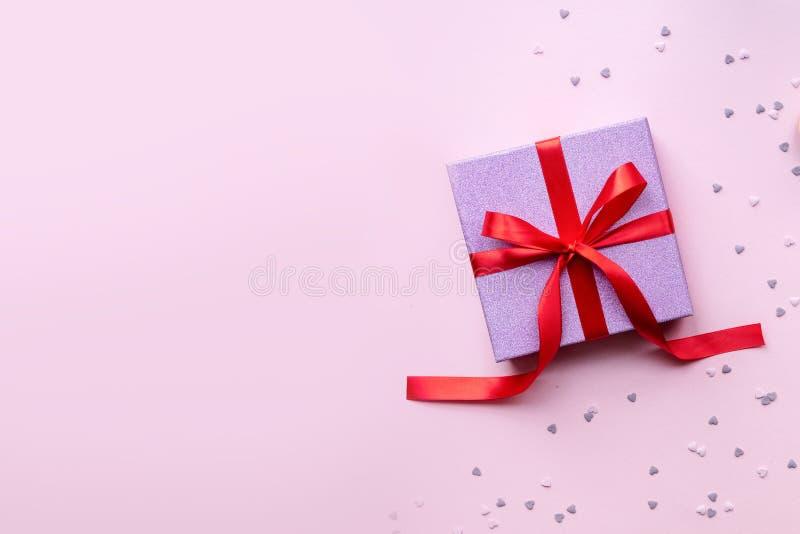 有红色丝带弓的桃红色礼物盒在桃红色背景 当前的节假日 免版税库存照片