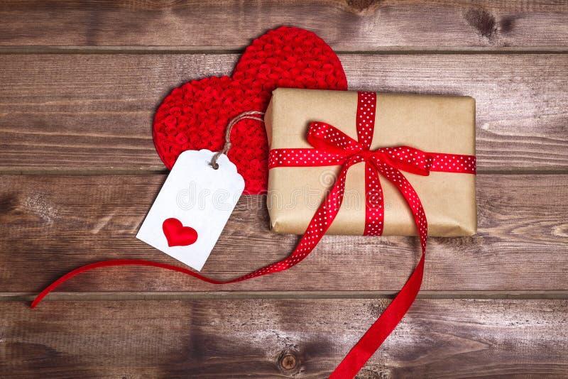 有红色丝带弓的被包裹的葡萄酒礼物盒和在木桌上的礼品券 免版税库存图片