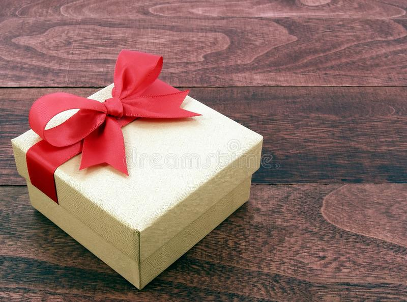 有红色丝带弓的金黄礼物盒在葡萄酒黑褐色木桌地板上 免版税图库摄影