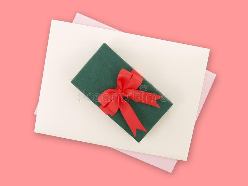 有红色丝带弓的绿色礼物盒和与浅紫色的贺卡的白色信封在桃红色背景 库存照片