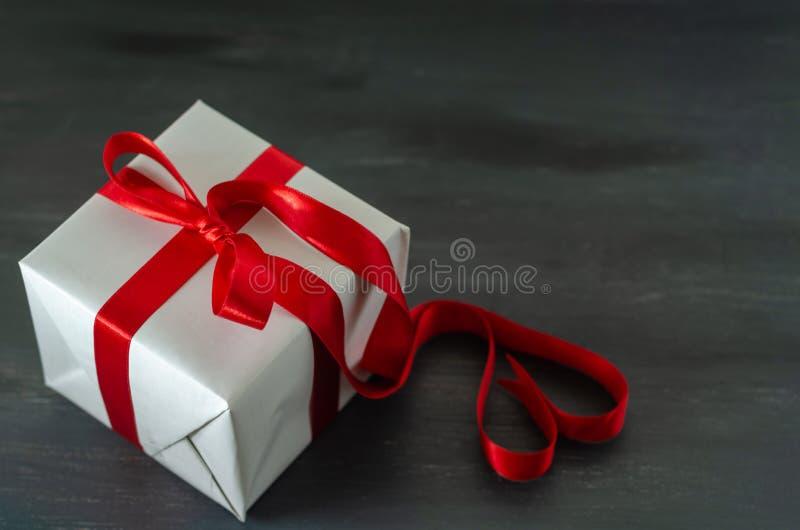 有红色丝带的在黑背景的礼物盒和弓 库存照片