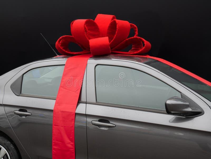 有红色丝带的灰色汽车在黑色 免版税库存照片