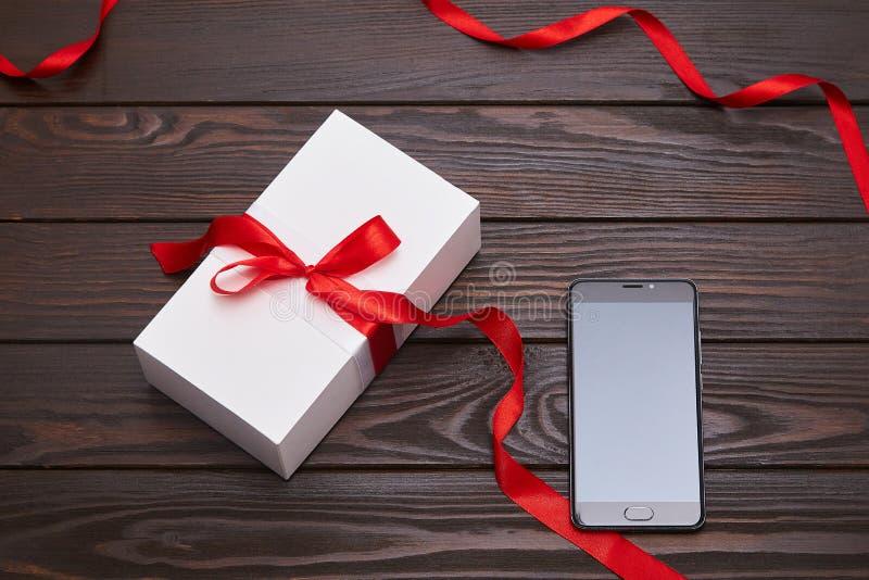 有红色丝带的白色在木背景的礼物盒和智能手机 免版税库存图片