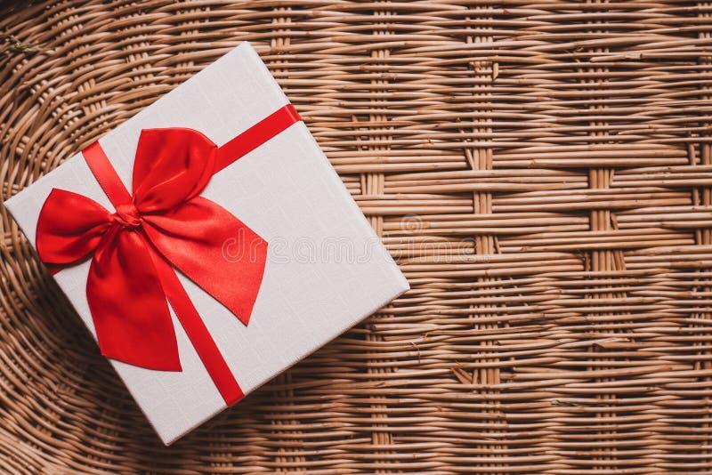 有红色丝带的礼物白色箱子在被编织的竹木背景舒适和温暖的家庭受欢迎的概念想法 免版税库存图片