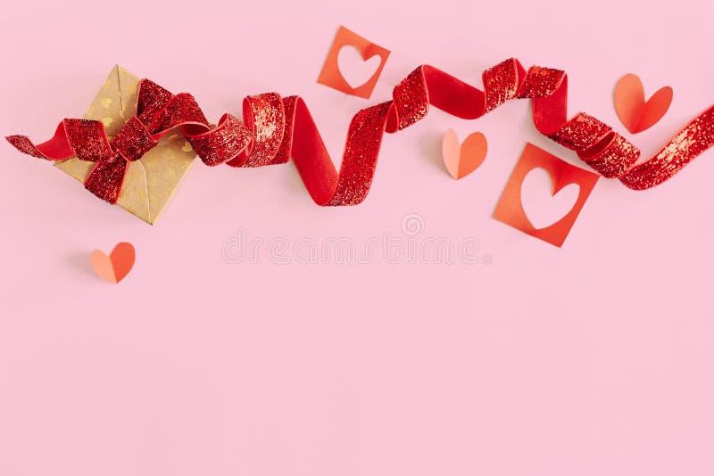 有红色丝带的礼物盒和在桃红色背景的红色纸心脏 情人节,爱,假日当前概念 库存图片