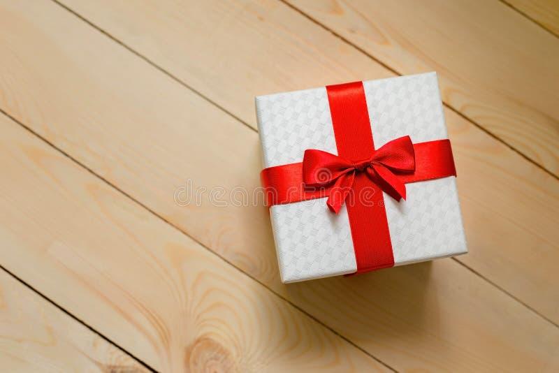 有红色丝带的礼物盒在木背景 免版税图库摄影
