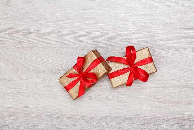 有红色丝带的礼物盒在灰色木板 免版税库存照片