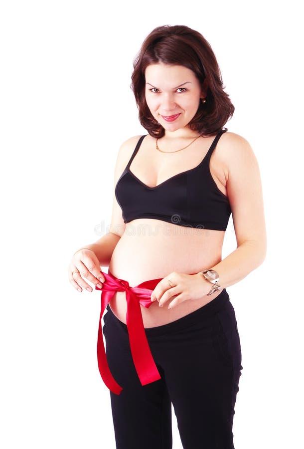 有红色丝带的美丽的孕妇 免版税库存照片