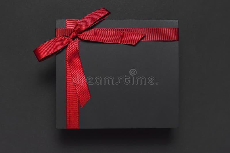 有红色丝带的黑礼物盒在黑暗的背景顶视图平的位置 假日概念,生日礼物,父亲节,华伦泰的D 免版税库存图片