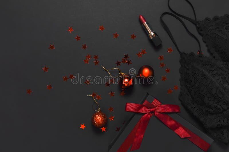 有红色丝带的,鞋带胸罩内衣,红色口红,圣诞节球,在黑暗的背景上面的全息照相的五彩纸屑黑礼物盒 免版税库存照片