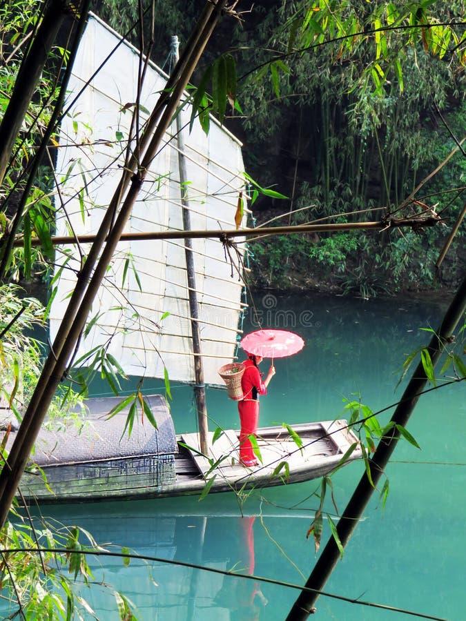 有红色伞的女孩在河船 库存照片