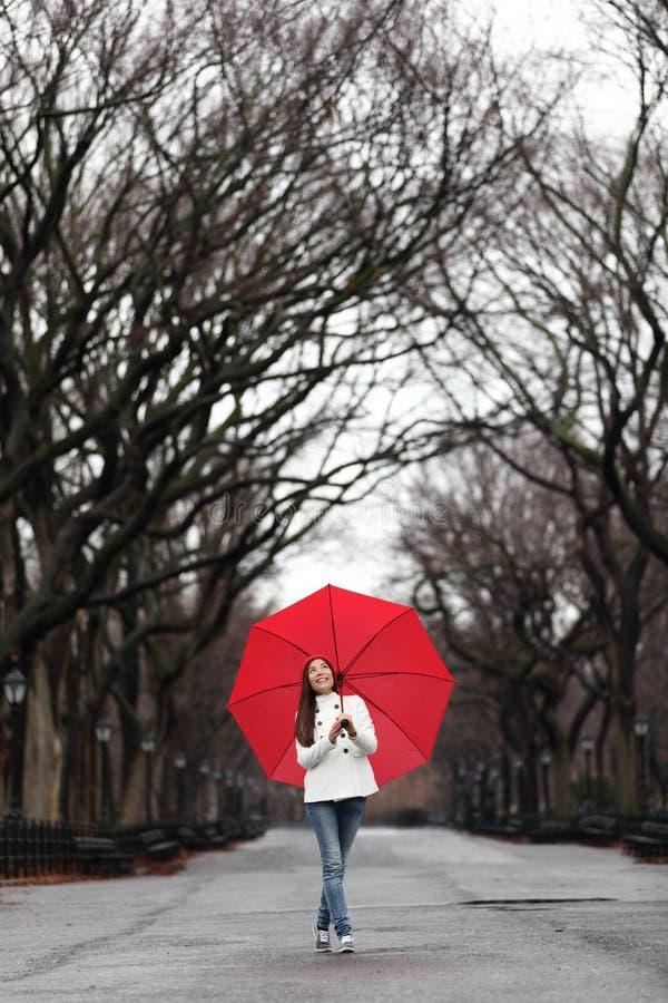 有红色伞的女孩走在秋天的公园的 免版税库存照片