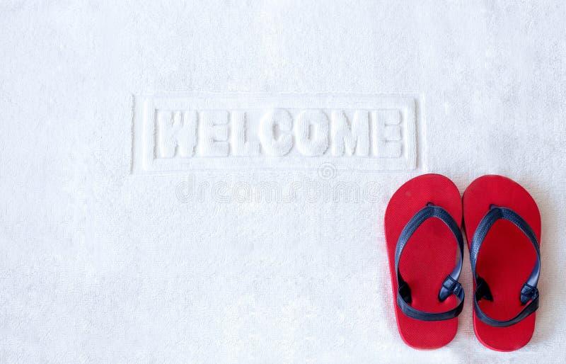 有红色儿童凉鞋的门垫 免版税图库摄影