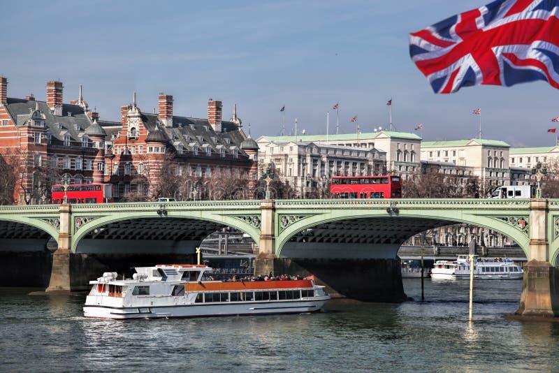 有红色公共汽车的桥梁反对城市游轮在伦敦,英国,英国 免版税库存照片