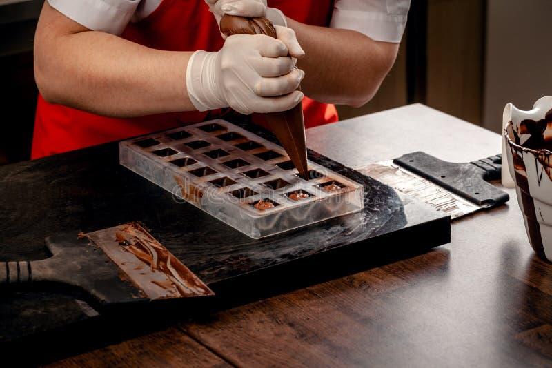 有红色制服的一名妇女糖果商和白色不育的手套做一套从牛奶巧克力的五颜六色的巧克力在a 库存图片