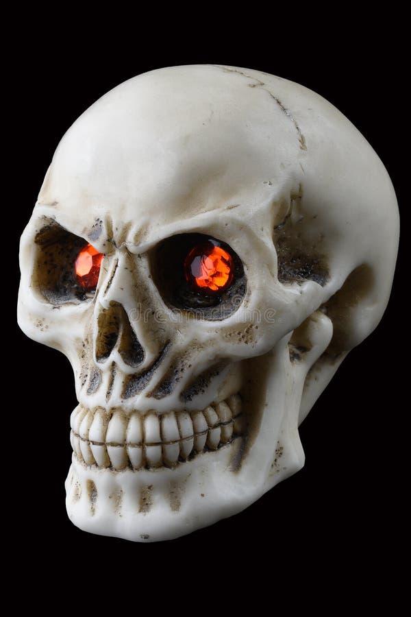 有红色发光的眼睛的万圣节头骨 裁减路线 库存照片