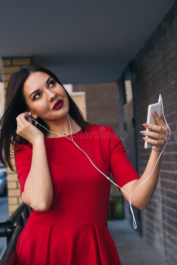 有红色口红的美女在红色礼服使用打电话和耳机 免版税图库摄影